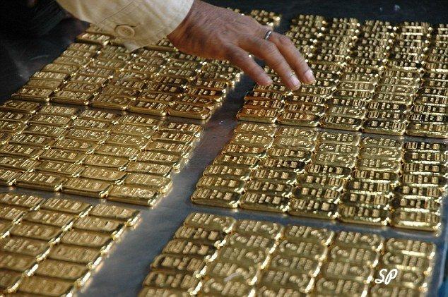 рука мужчины трогает контрабандное золото высшей пробы на столе