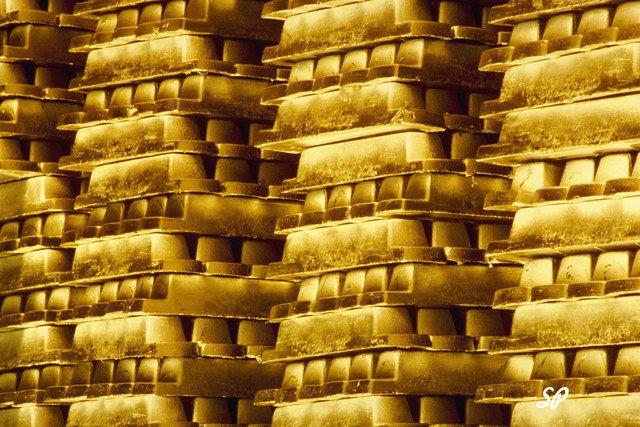 Золотые слитки сложены в ряд друг на друга в большом количестве