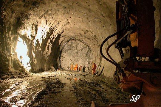 прокладка туннеля через горные породы, рабочие стоят в спецодежде