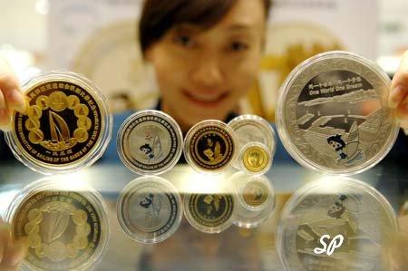 коллекционные монеты в пластиковых упаковках на первом плане, на втором плане китайская девушка улыбается