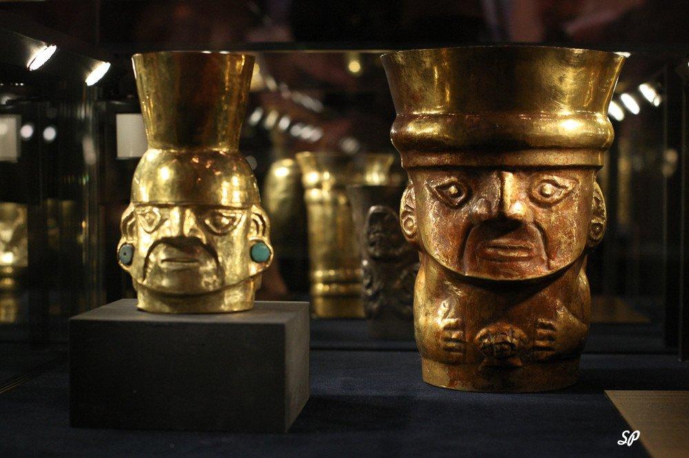 золотые кубки в форме статуеток. расположенные под музейной витриной