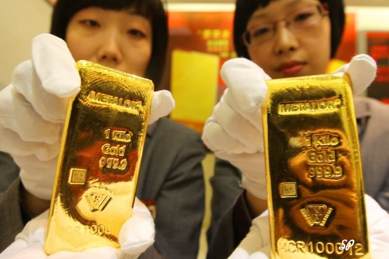 китайские девушки в белых перчатках держат слитки золота