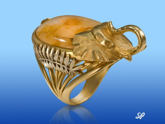 Золотое кольцо в фольклорном стиле, украшенная головой слона из золота, крупным полудрагоценным камнем и белым золотом на голубом фоне