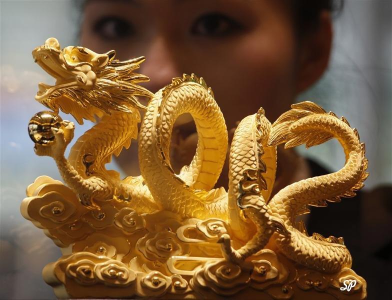 Китайский сказочный дракон из золота, а на заднем фоне лицо китайской девушки