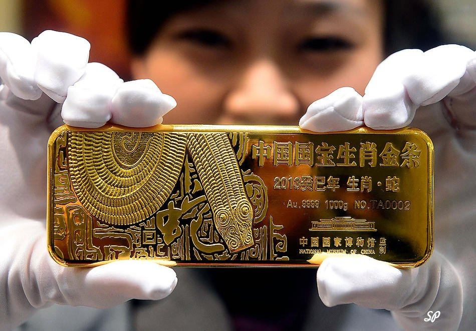 Красивая китайская девушка в белых перчатках держит слиток золота