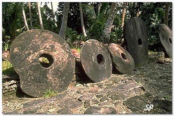 Плоские большие камни круглой формы о отверстием в центре, расположенные на земле в тропическом лесу