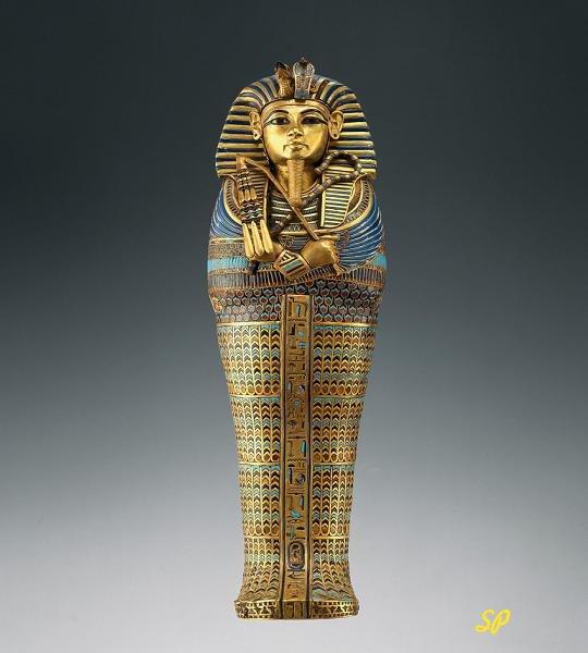 Золотой саркофаг египетского фараона-бога на сером фоне, украшенный нефритом и другими камнями