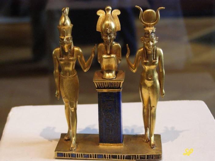 Две золотые древнеегипетские статуэтки на подставке из золота , а между ними третья золотая статуэтка в виде бюста фараона на пьедестале