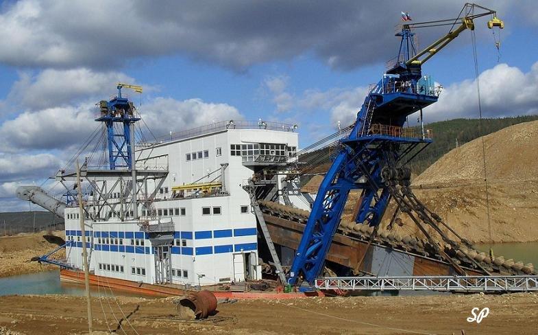 Вид иркутского золотого рудника на фоне леса, с расположенными там различными золотодобывающими механизмами, выкрашенными в белый и синий цвета