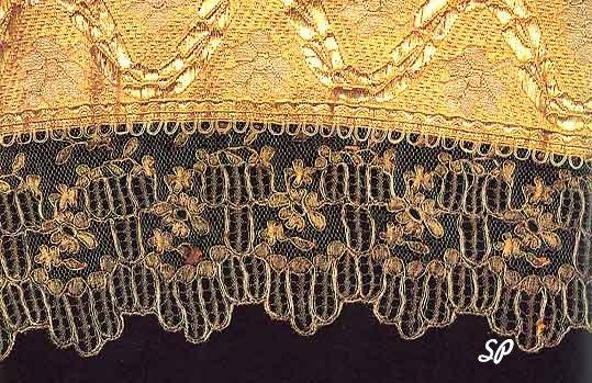 Кружево из золотых нитей, прикрепленной к расшитой золотом ткани на черном фоне