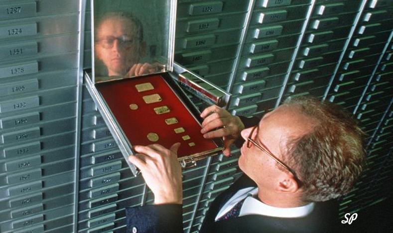 Стена из банковских ячеек с одной открытой, в которую мужчина ставит золотые слитки и монеты