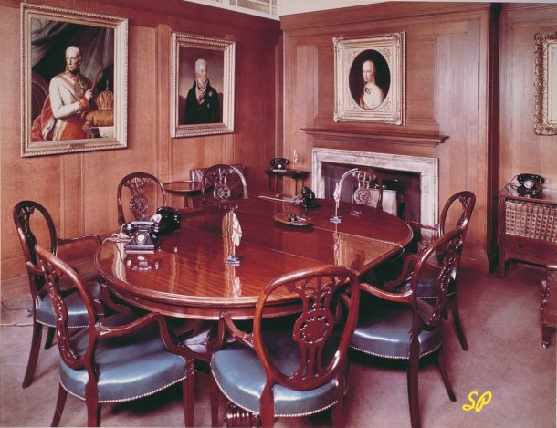 Комната, стены которой украшены картинами политических деятелей прошлого, а в середине стоит большой овальный стол в окружении резных стульев