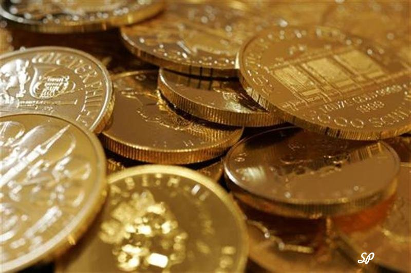 Много золотых монет, беспорядочно разбросанных друг на друге и сфотографированных с близкого расстояния
