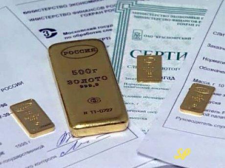 Один большой и три маленьких золотых слитка с надписью «Россия» и «золото» на русском языке, расположенные на банковских документах обезличенного металлического счета.