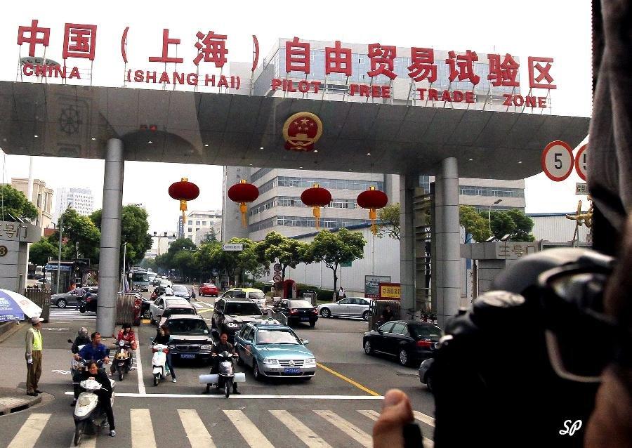 Вид красивого проспекта в Шанхае с проезжающими там машинами и мотоциклами с большой аркой, на которой китайскими иероглифами и английскими буквами написано: Китай, Шанхай, свободная торговая зона