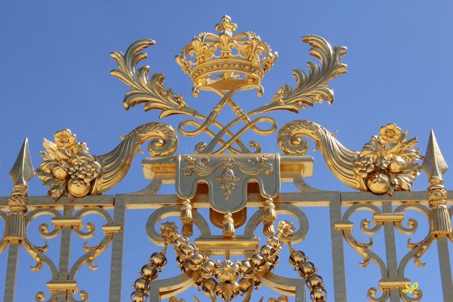 Фрагмент золотых ворот в Шато де Версаль в Париже, богато украшенные золотыми завитушками, цветочками, гнутыми прутьями, короной, гербом и прутьями в виде наконечника копья