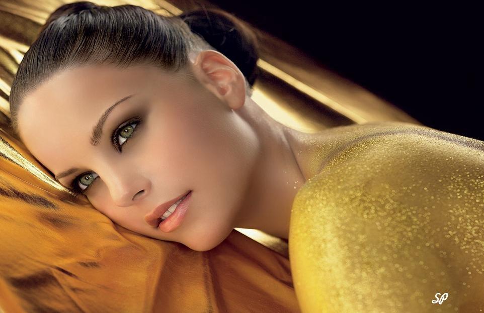 Фото красивой девушки, лежащей на животе на поверхности, покрытой тканью золотого цвета. Спина девушки покрыта мазью с частицами золота