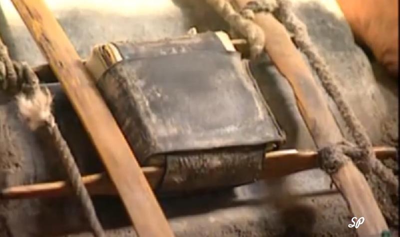 Устройство в виде деревянной рамки. стянутой толстыми веревками, в середине которой находится завернутая в бычий кишок стопка бумаги