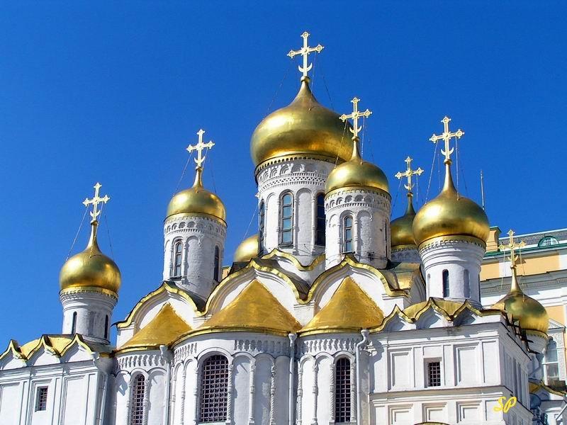 Вид белокаменной православной церкви с золотыми куполами крупным планом