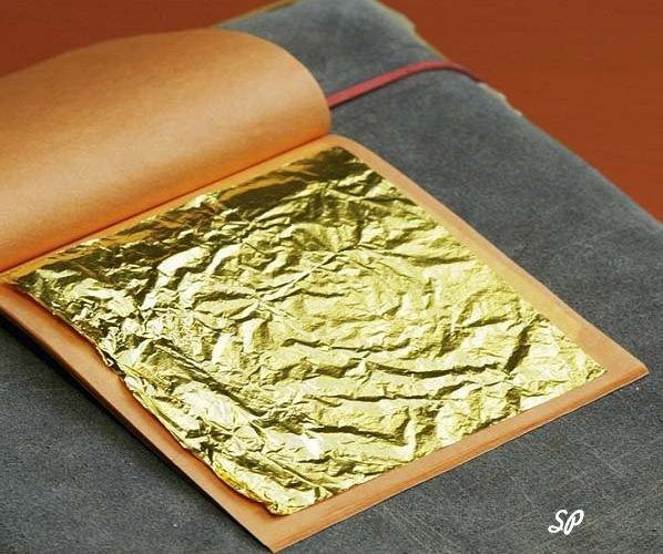 Квадратная пластинка сусального золота лежащая на листке раскрытой «книжки» в виде блокнотика