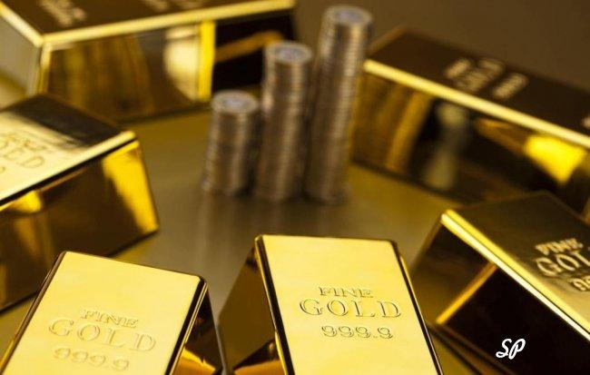 Стопки золотых монет в окружении золотых слитков