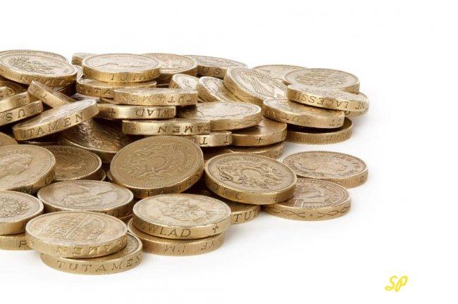 Россыпь золотых монет на белом фоне