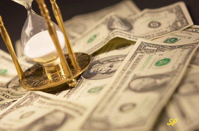 песочные часы на долларовых купюрах