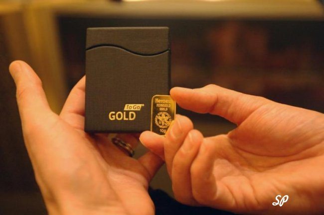 Миниатюрный золотой слиток в руках