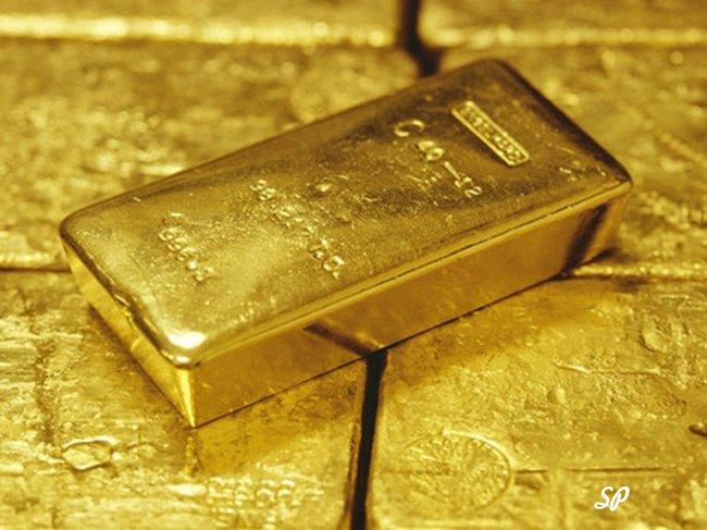 Золотой слиток на фоне других слитков