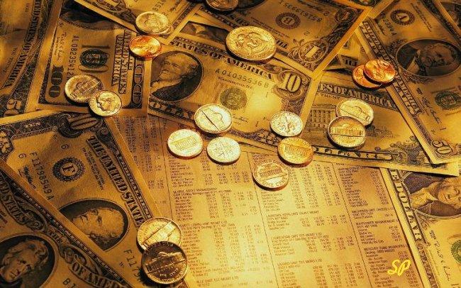 Россыпь золотых монет и купюр долларов США