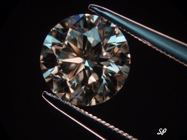 Алмаз в щипцах на чёрном фоне