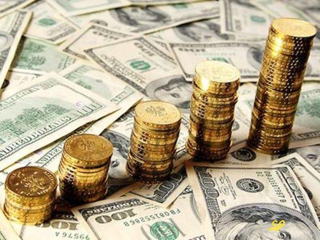 Золотые монеты на фоне купюр долларов США
