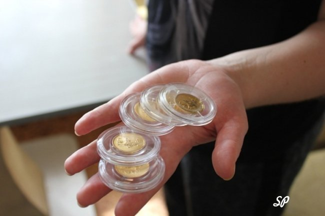 Золотые монеты в упаковке в руках