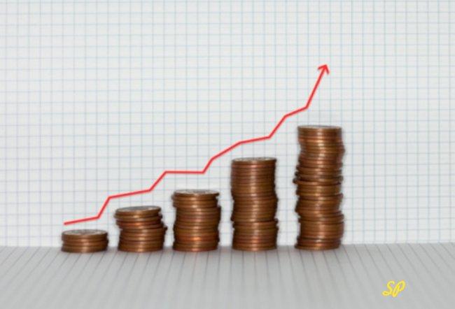 График из стопок золотых монет на сером фоне