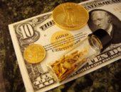 Золотые монеты и золотая россыпь в баночке на фоне купюры доллара США