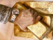 Рука на слитках золота