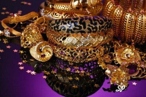 Золотые украшения разных видов и размеров на фиолетовой ткани