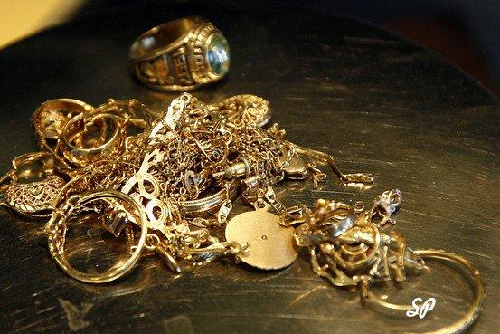 золотые украшения вперемешку лежат на столе на темной поверхности