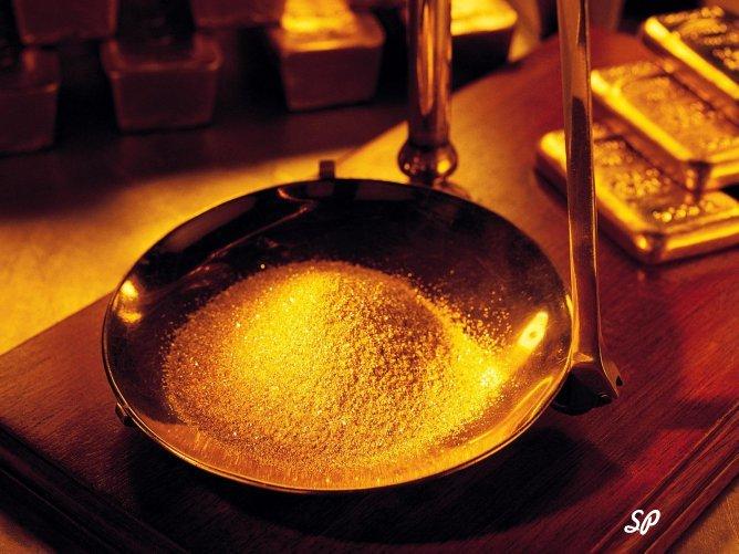 золотой песок на медной чаше весов, стоящих на столе