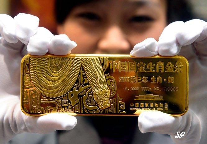 девушка держит золотой слиток с китайскими узорами в руках с белыми перчатками