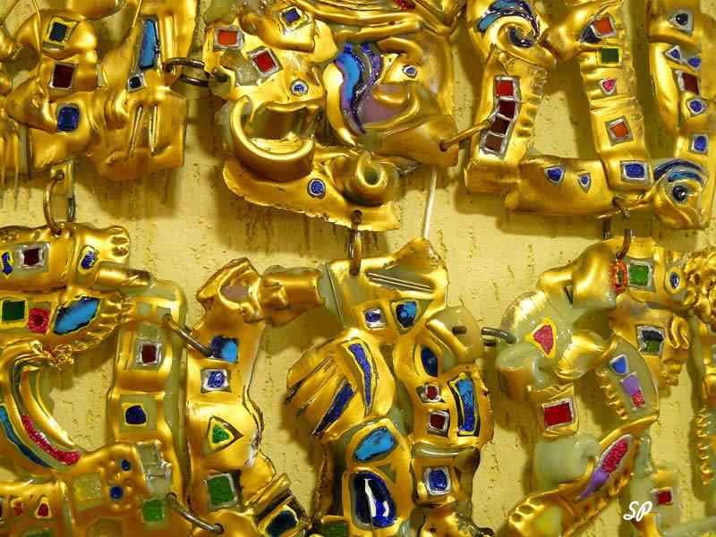 большое количество золотых украшений с разноцветными драгоценными камнями