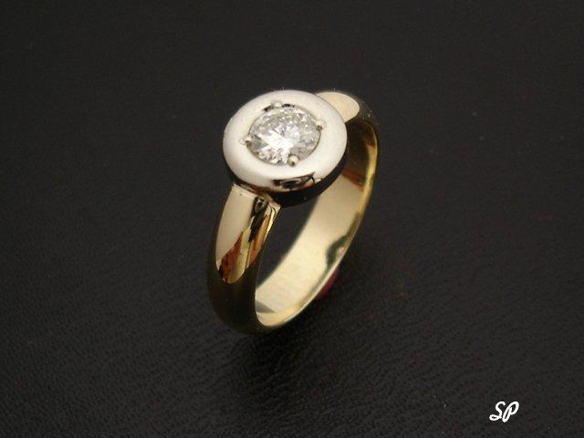 классическое золотое кольцо с крупным белым бриллиантом в ободке из белого золота на черном фоне