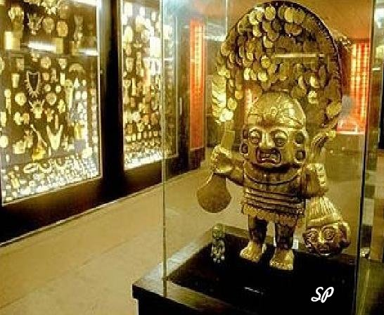 Золотая статуэтка инков в музейной витрине, а на заднем плане другие золотые предметы инков