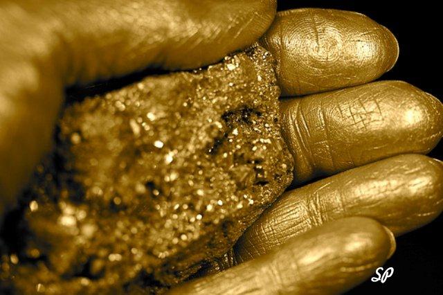 Золотая человеческая рука на черном фоне, держащая в ладони золотой песок