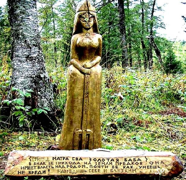 Золотая статуя женщины в полный рост, расположенная в лесу на пьедестале, на котором высечен русский текст