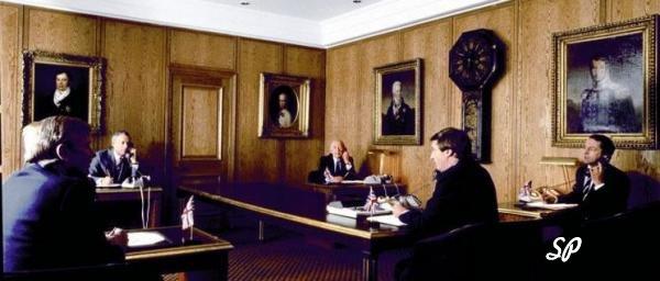 Пять участников лондонского золотого фиксинга, сидящие за отдельными столами в большом кабинете, стены которого украшены картинами деятелей прошлого