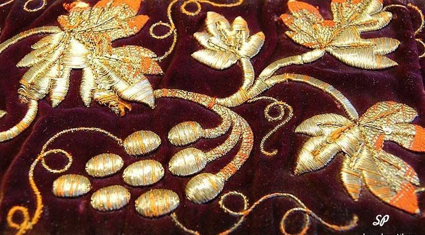 Ткань темного бордового цвета, расшитая золотыми нитями в виде цветочного узора