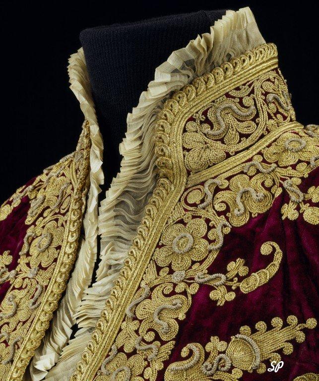 Образец одежды придворных 17 века из бордовой ткани, расшитая золотыми нитками и надетая на манекен