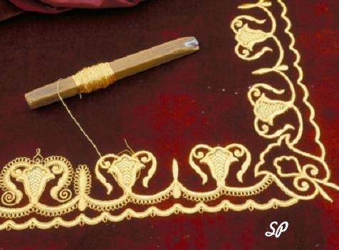 Уголок темной бордовой ткани, расшитой золотыми нитками, на которой лежит маленько веретено с нитью из золота