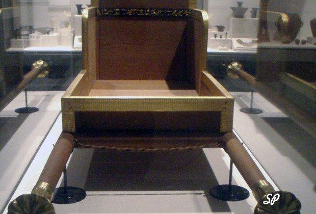 Позолоченные носилки древнеегипетских фараонов, выставленная в музейной витрине, на заднем плане виднеются другие экспонаты